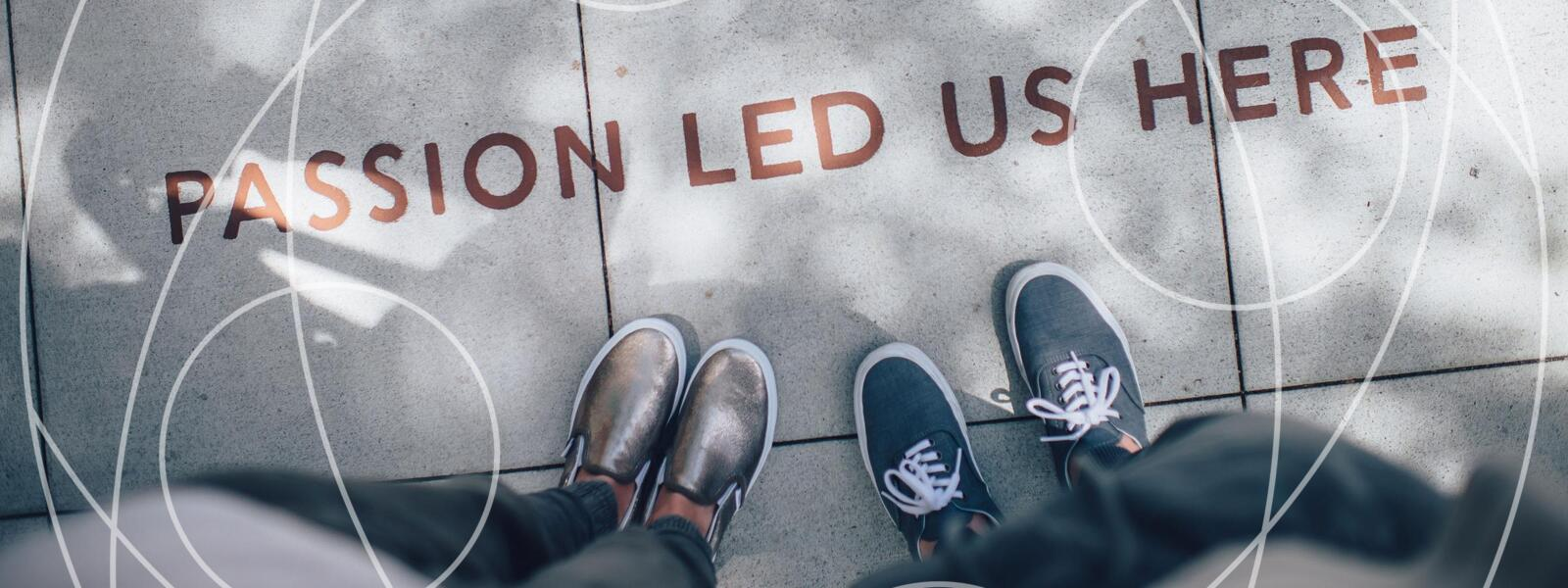 two students' shoes standing in front of sidewalk art reading, 'passion led us here'