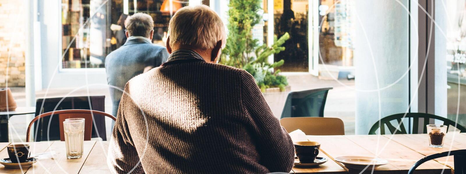 older man's back turned to viewer, studying and reading in coffee shop