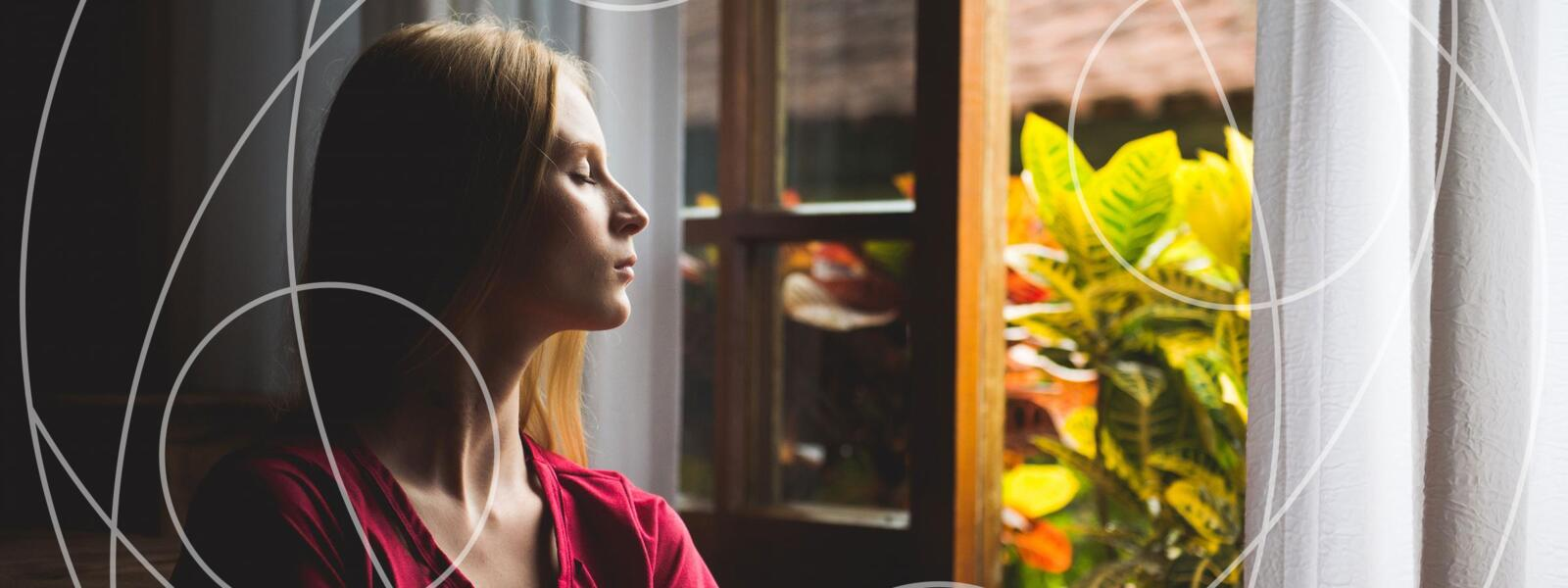 Woman sits by an open window, eyes closed, meditating
