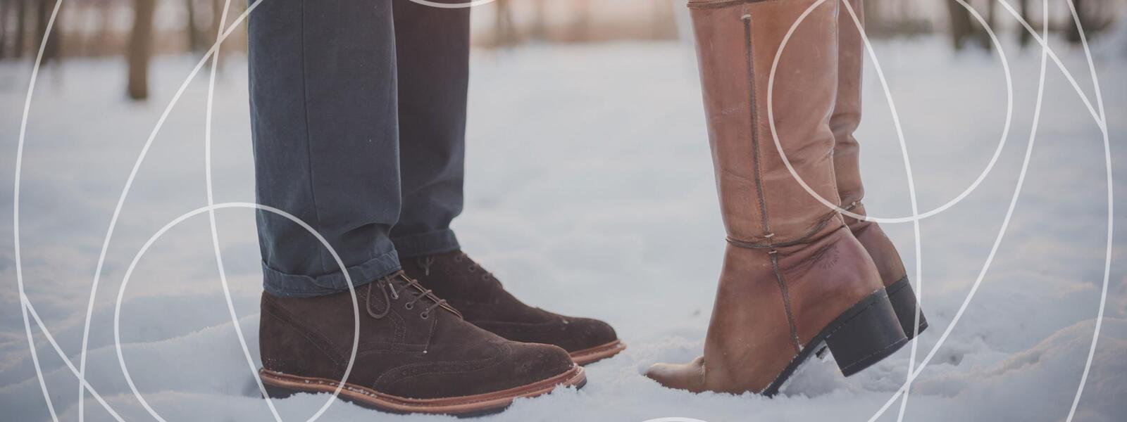 Man's brown boots stand across from woman's brown boots in snow. Woman is on tip toes. Implying a kissing couple up top.