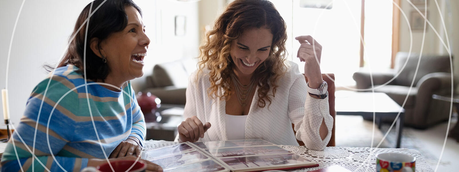 adult daughter laughing with mom about photo album