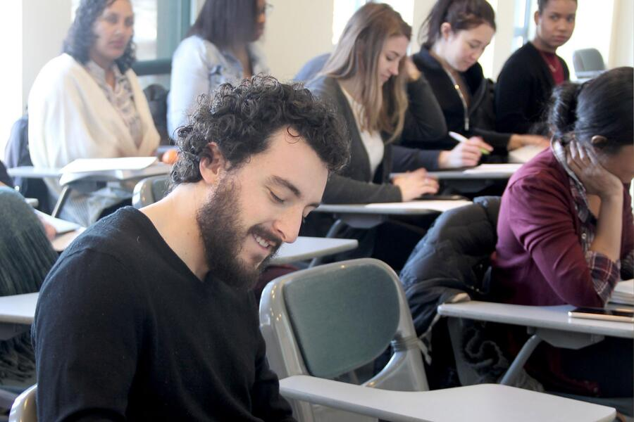 male graduate student in the forefront of students in a lecture room at northwestern
