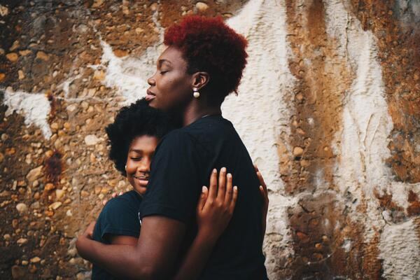 mother and daughter embrace in front of brick wall