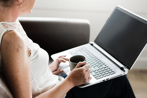 woman holding mug and computer on couch